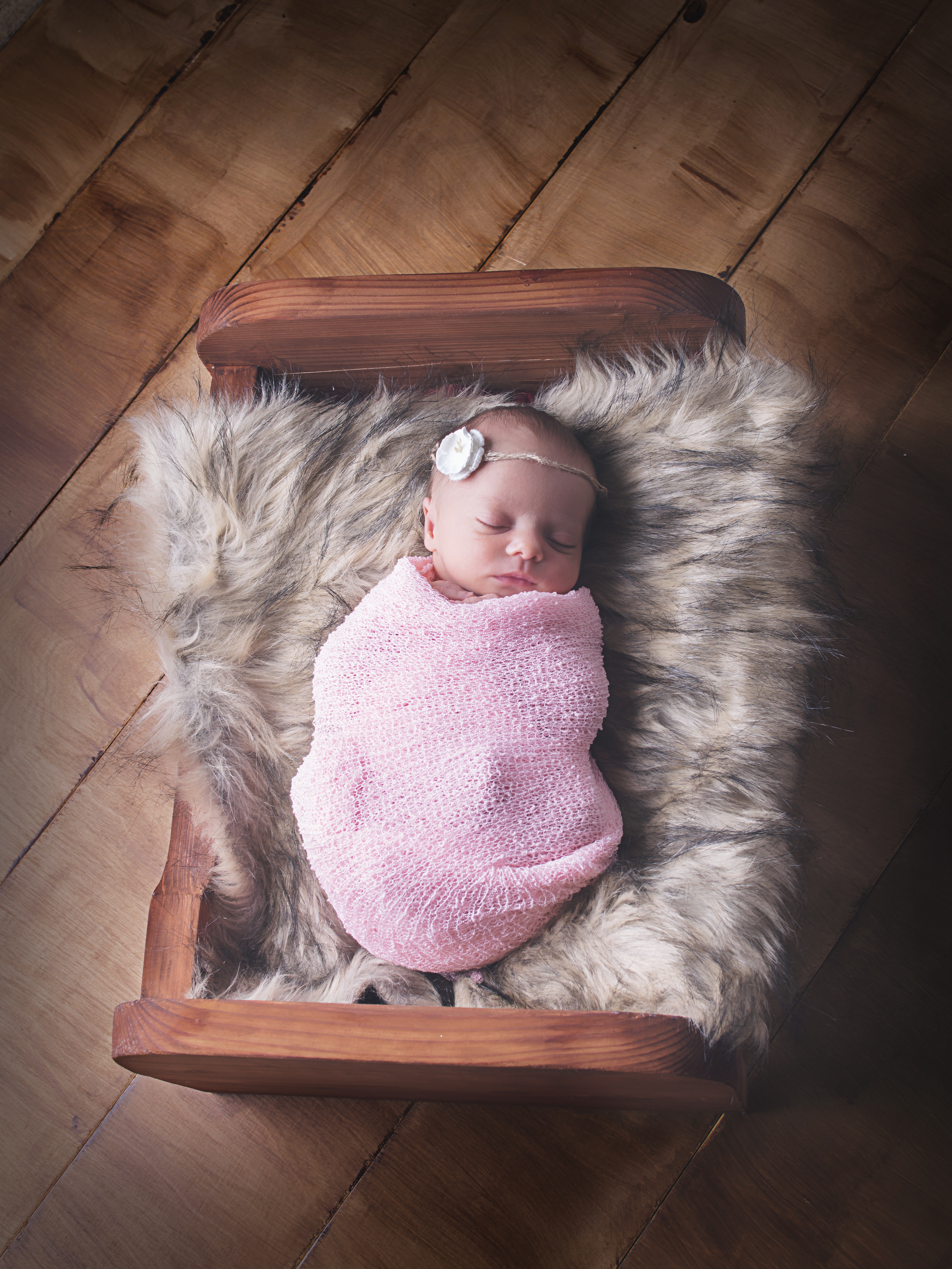 Newborn baby in little wooden bed