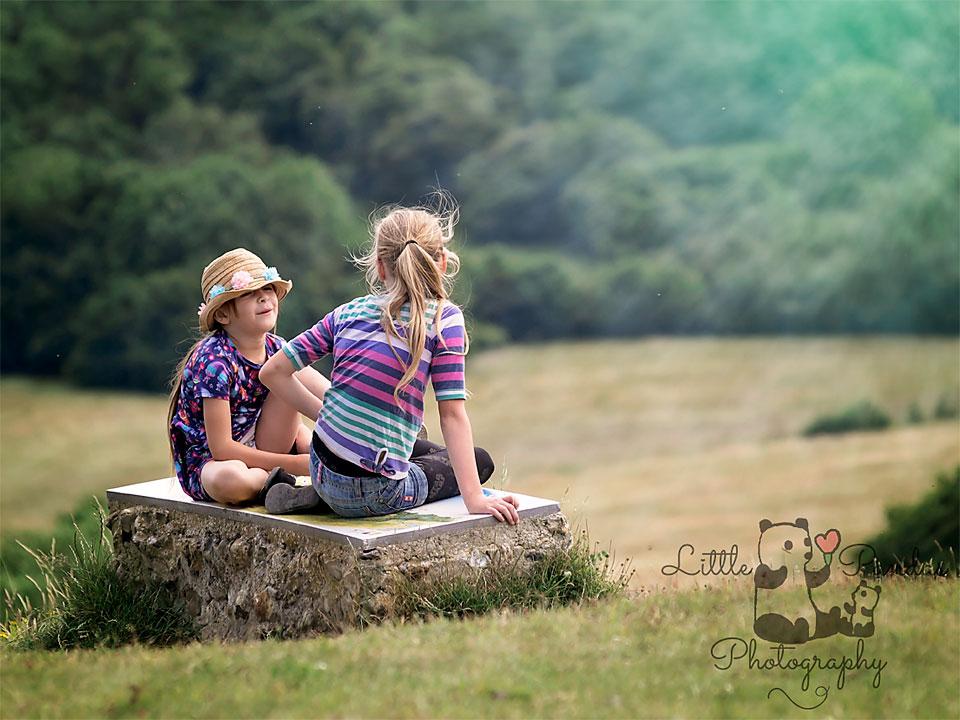 Little girls sitting on a rock