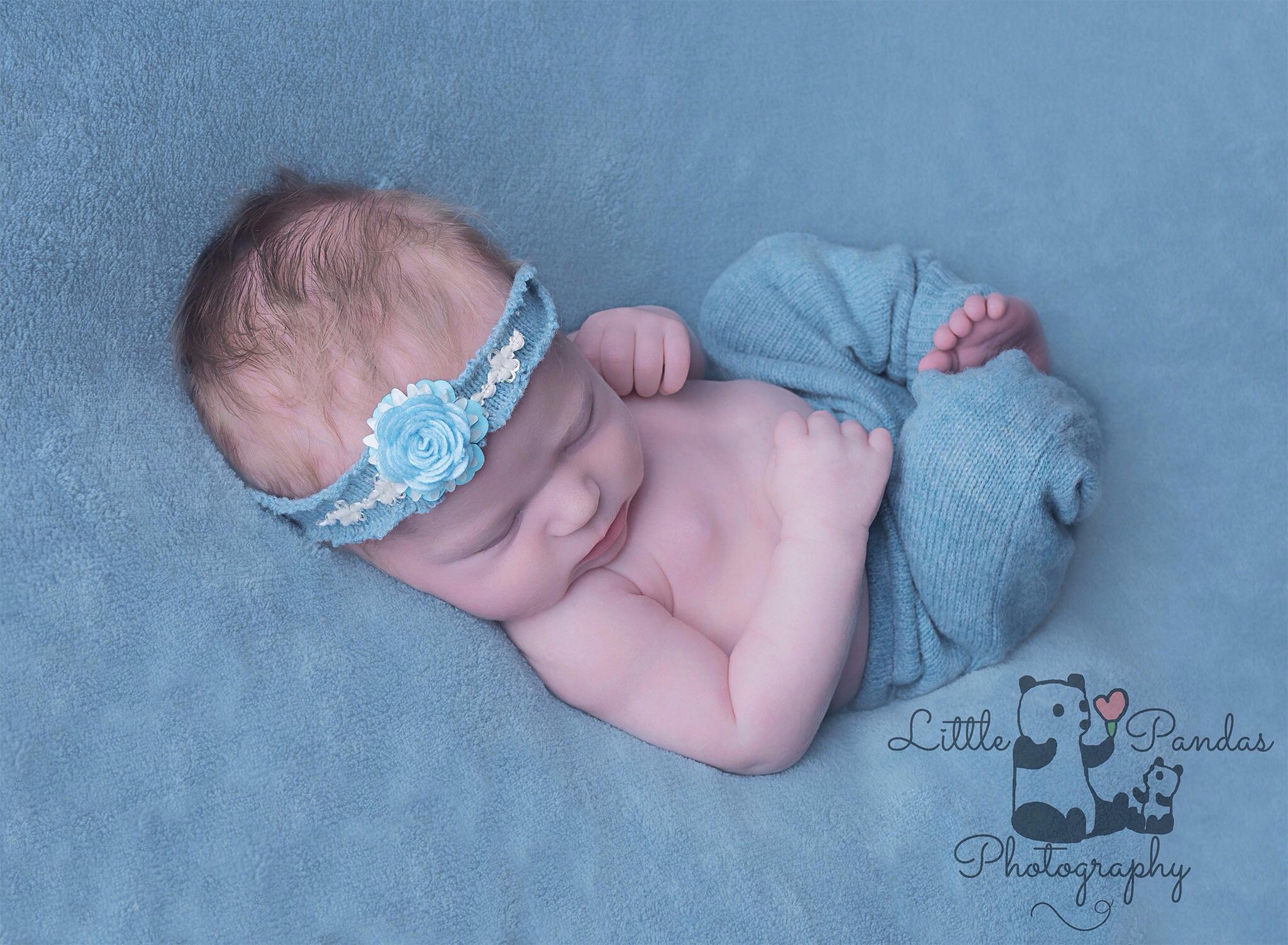 Baby girl in aqua asleep on back